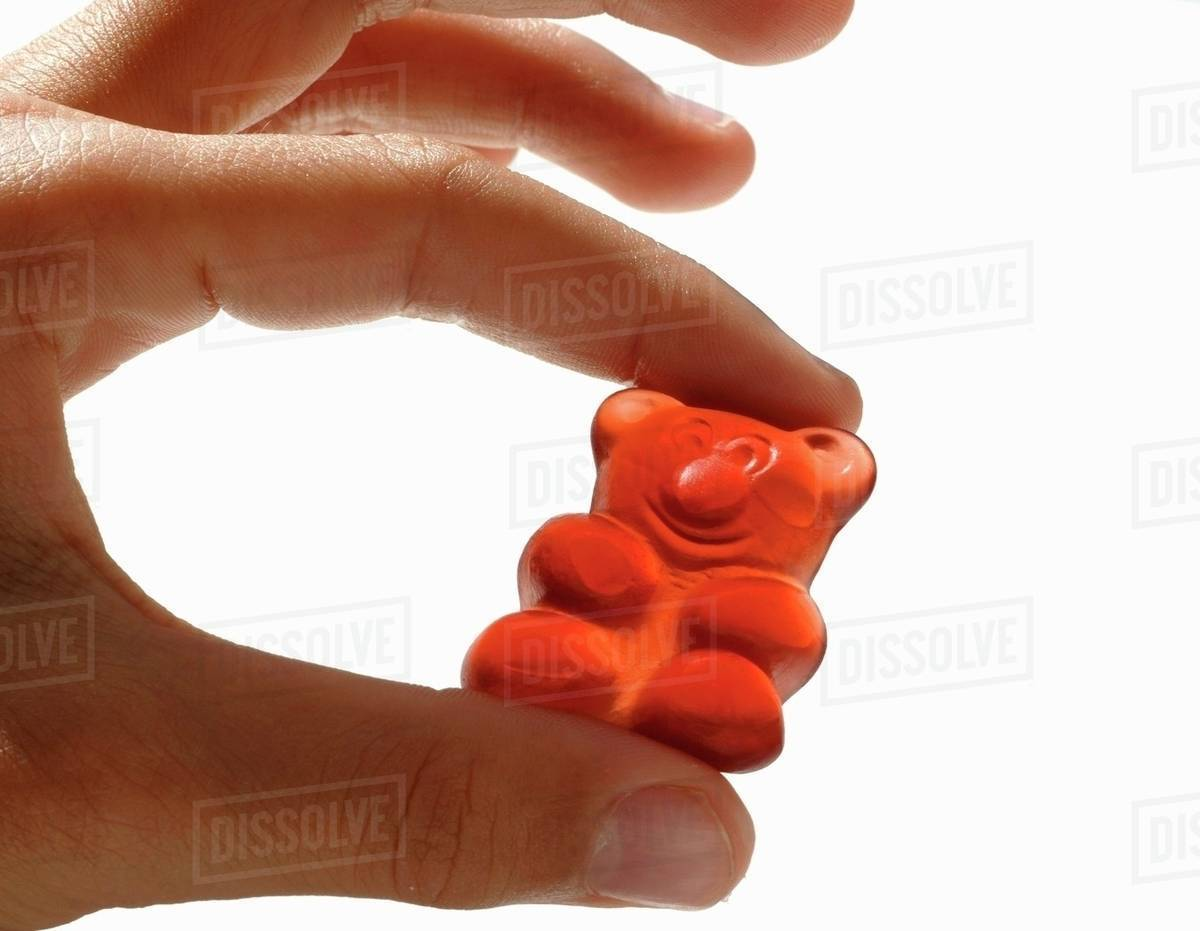 Hand Holding A Gummi Bear Stock Photo Dissolve Wrist Red