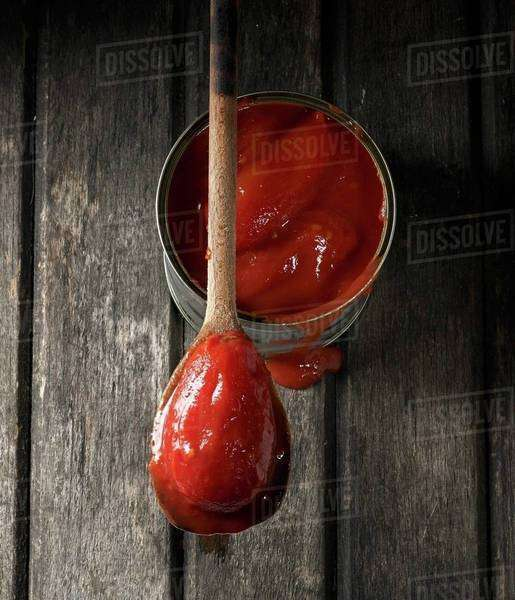 A tin of whole tomatoes with one on a wooden spoon Royalty-free stock photo
