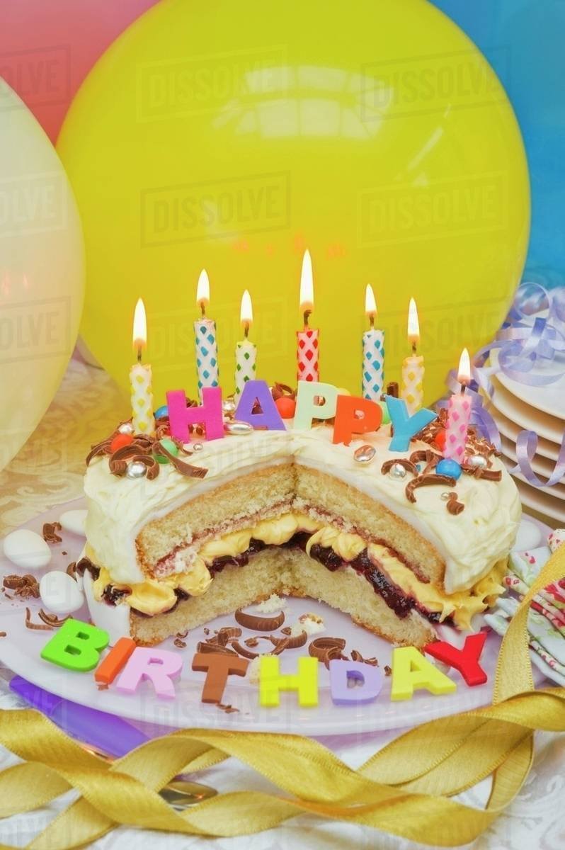 Sponge Layer Cake With Candles For A Birthday And Balloons
