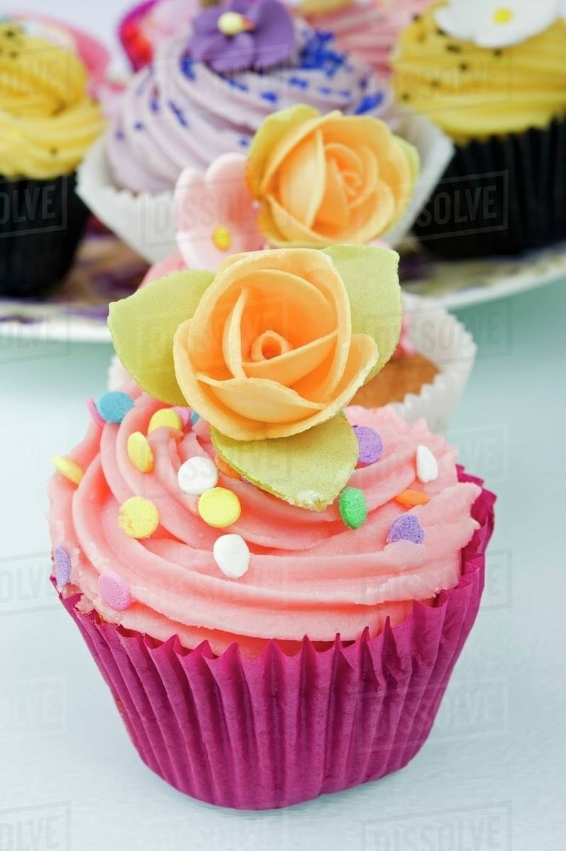 Still Life Of A Row Coloured Cup Cakes Decorated With Orange Rose Flowers On Top In Their Cake Papers White Table Other The