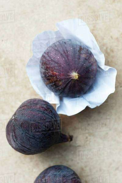 Three figs, one on paper Royalty-free stock photo