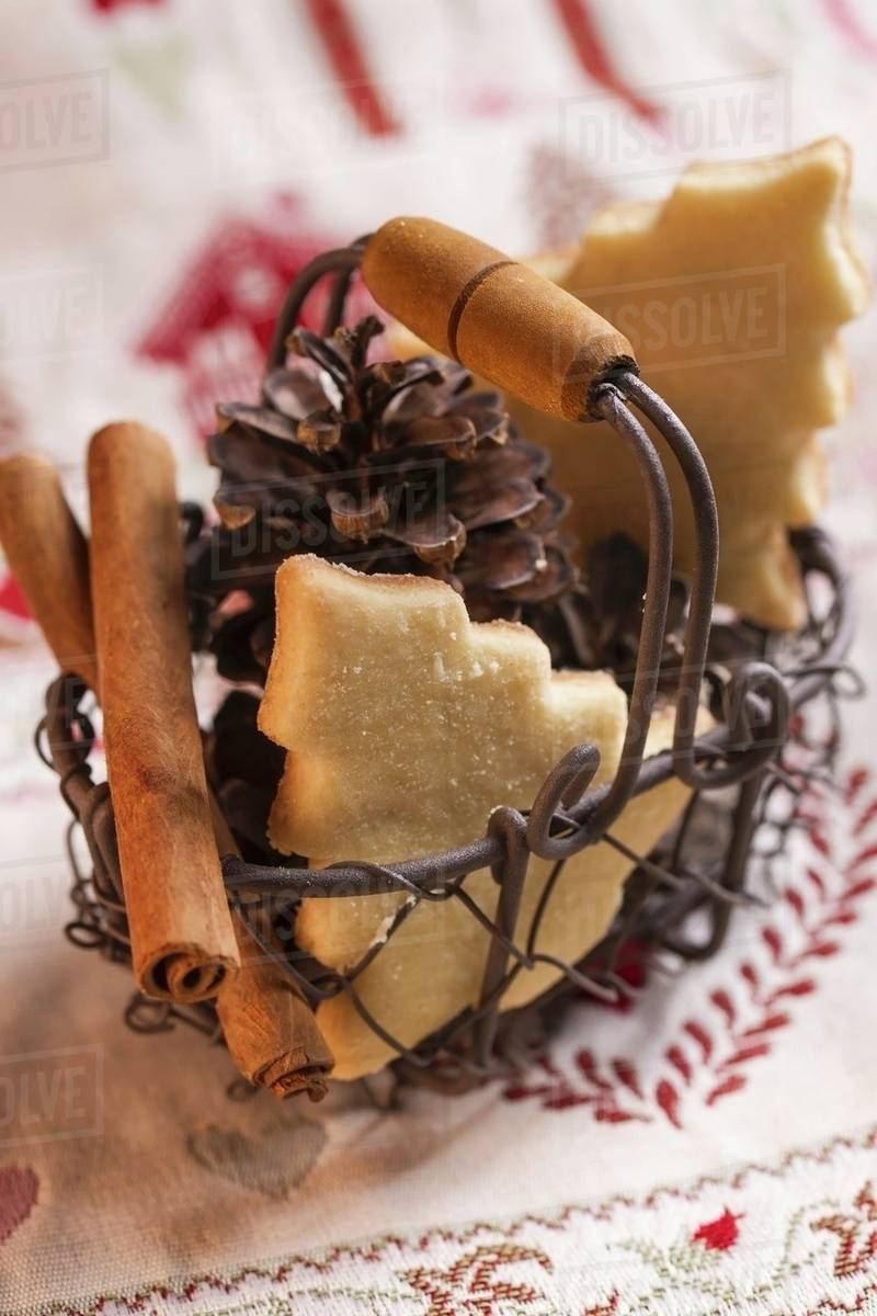 A Wire Basket Of Christmas Biscuits Pine Cones And Cinnamon Sticks Stock Photo
