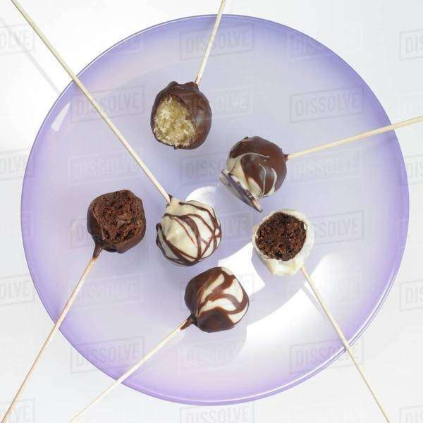 Cake pops with chocolate icing, one with a bite taken out Royalty-free stock photo