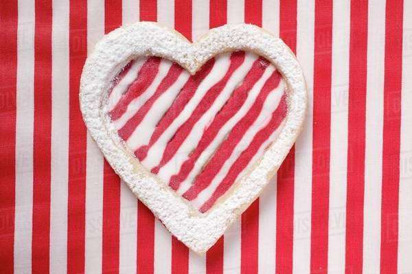 Heart-shaped biscuit with red and white striped icing Royalty-free stock photo