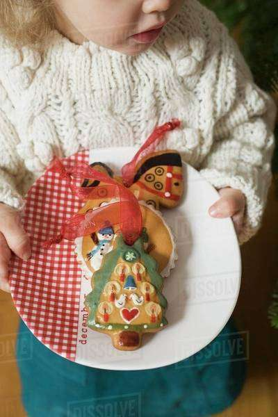 Small girl holding plate of gingerbread tree ornaments Royalty-free stock photo