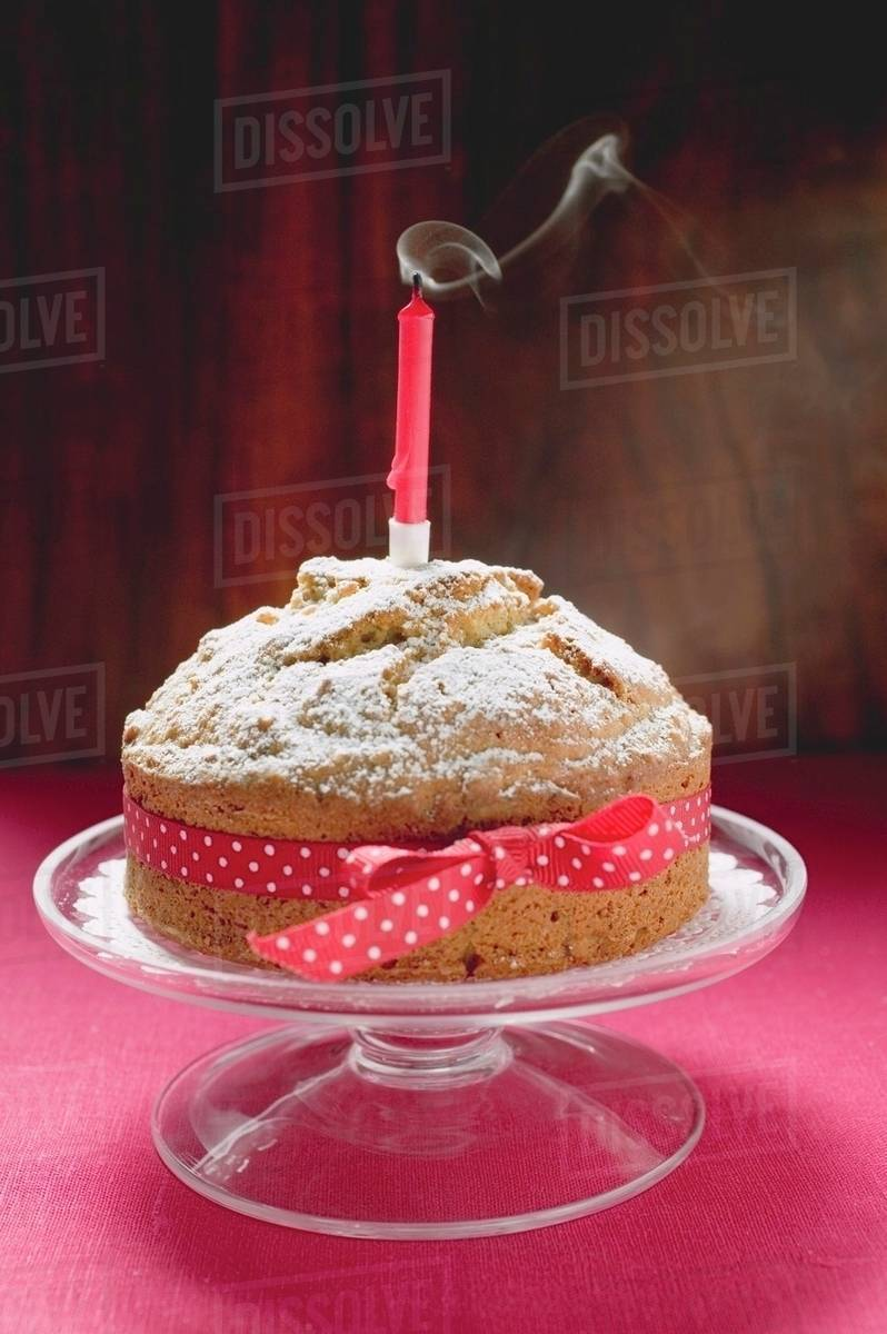 Birthday Cake With Red Bow And Blown Out Candle Stock Photo Dissolve