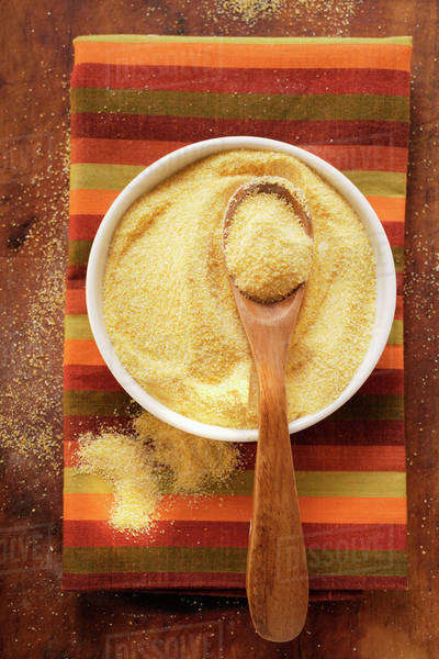 Polenta in bowl with wooden spoon on coloured cloth Royalty-free stock photo