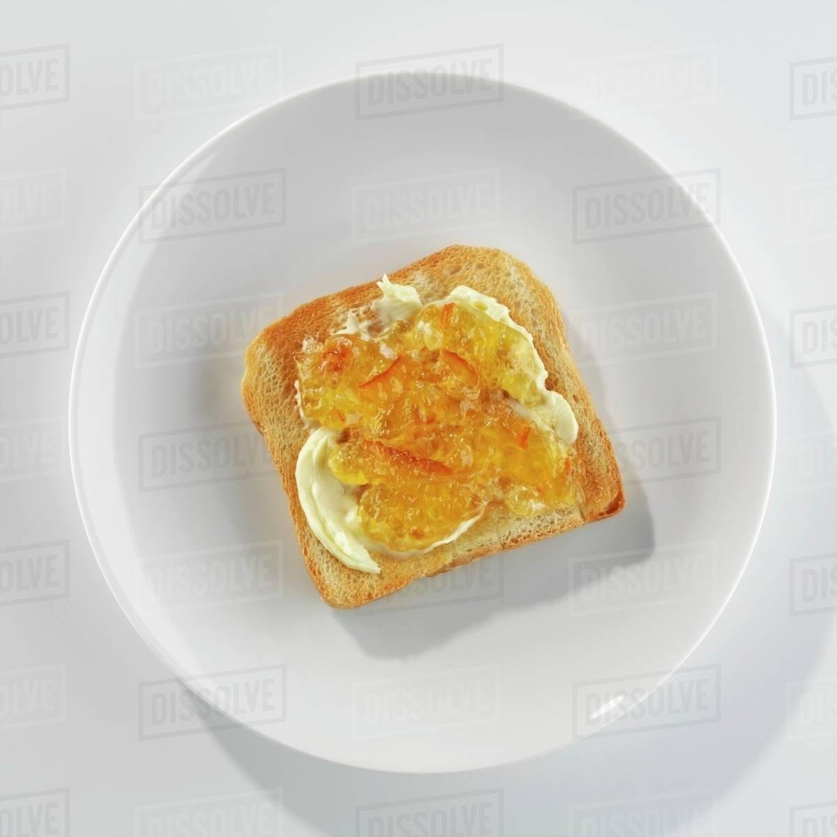 a slice of toast with butter and marmalade on a plate stock photo