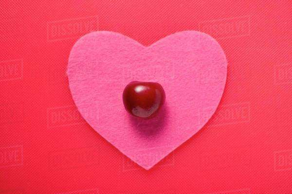 A cherry on a pink fabric heart Royalty-free stock photo