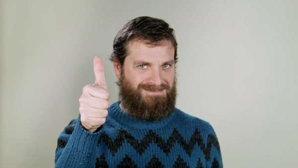 Hipster man showing thumbs up, saying ok. Close-up on neutral background Royalty-free stock video