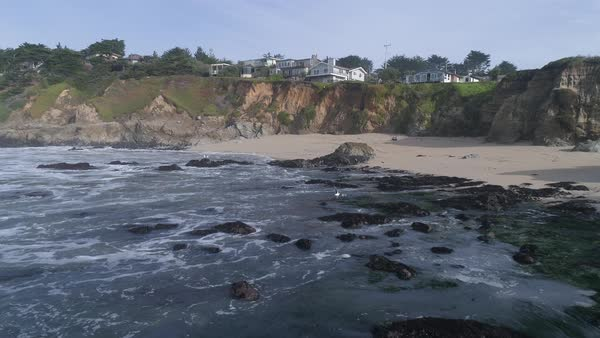 View of Half Moon Bay beach with cliff and houses in background Royalty-free stock video