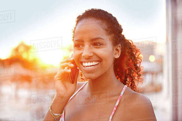 Happy young woman on cell phone at sunset Rights-managed stock photo