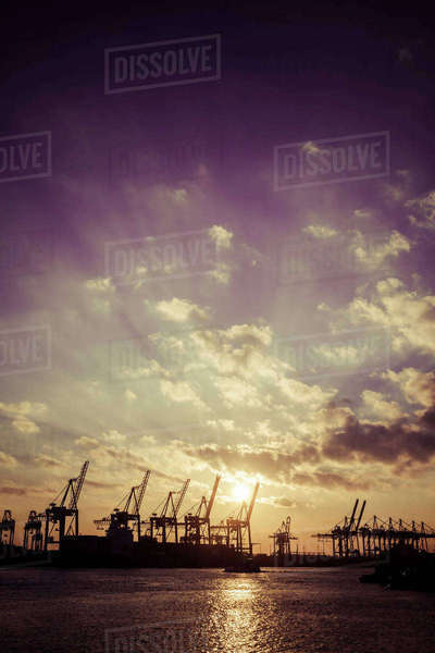Germany, Hamburg, container cranes at sunset Rights-managed stock photo