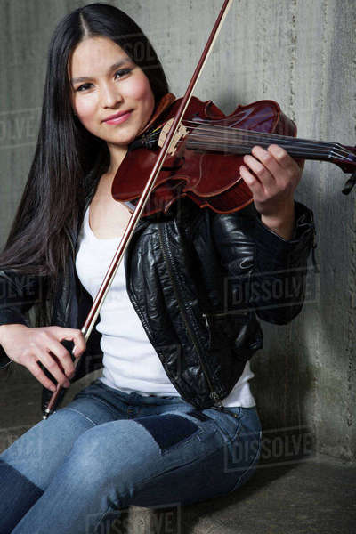 Portrait of young female Asian violinist in front of concrete wall Rights-managed stock photo