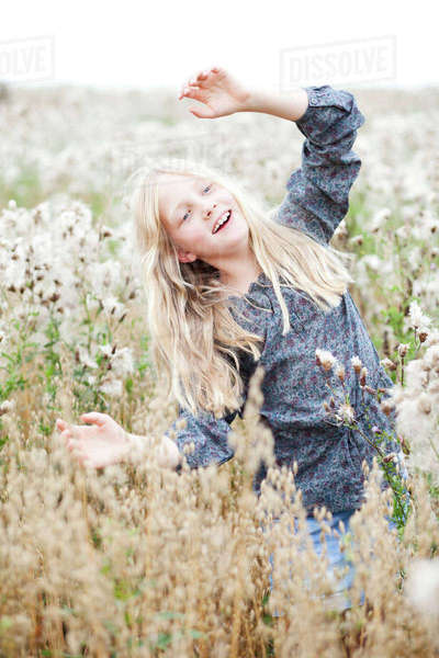 Portrait of smiling girl having fun in a field Rights-managed stock photo