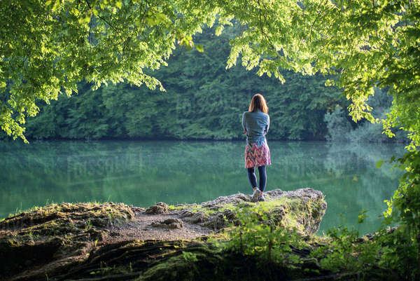 Germany, Bavaria, back view of a woman standing at a lake Rights-managed stock photo