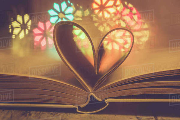 Heart shaped book pages in front of colourful lights Rights-managed stock photo