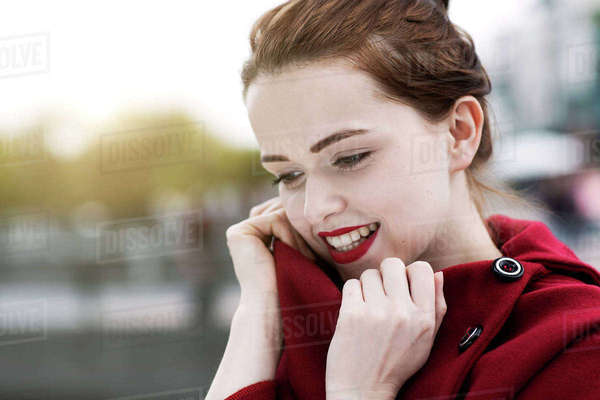 Portrait of daydreaming young woman with red lips wearing red cape Rights-managed stock photo