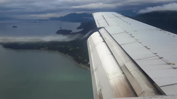 View of airline wing at full flap with vapor trails streaming from the end of the flaps on cloudy day as the aircraft passes over boats in the channel on approach to Juneau, Alaska. Royalty-free stock video
