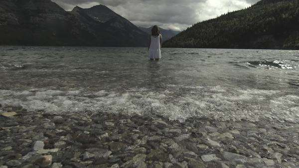 Handheld shot showing the back of a woman standing in water in front of a mountain landscape Royalty-free stock video