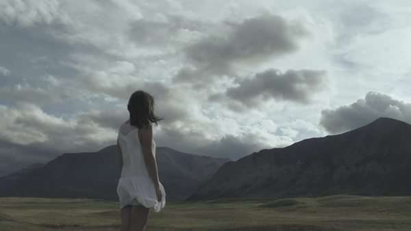 Handheld shot showing a woman in white dress standing on a field Royalty-free stock video