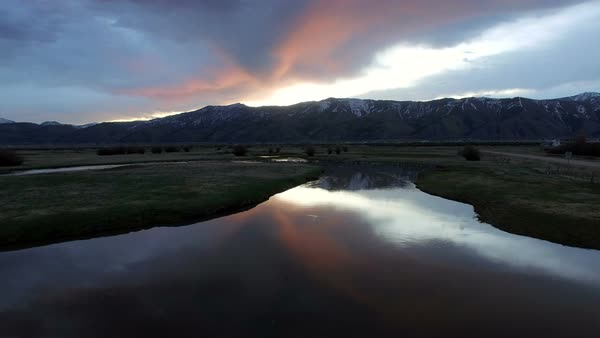 Flying view over river as sun is lighting up clouds in Wyoming Royalty-free stock video