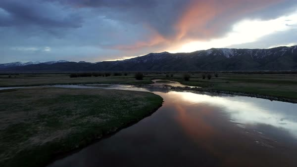Drone flying backwards as sun is lighting up clouds over river in Wyoming. Royalty-free stock video