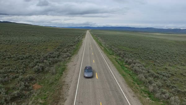 Drone in front of car on road in a vast landscape as it drives. Royalty-free stock video