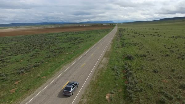 Drone following car on road in a vast landscape at high speed Royalty-free stock video