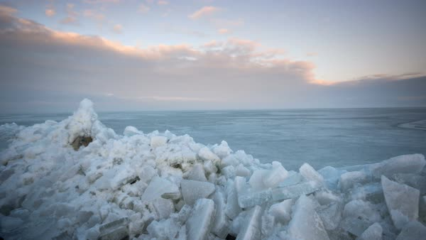Timelapse viewing ice piles on the edge of Utah Lake as the sun lights up the clouds. Royalty-free stock video