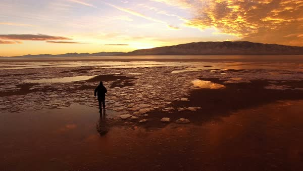 View of man walking through icy landscape during colorful sunset in Utah. Royalty-free stock video