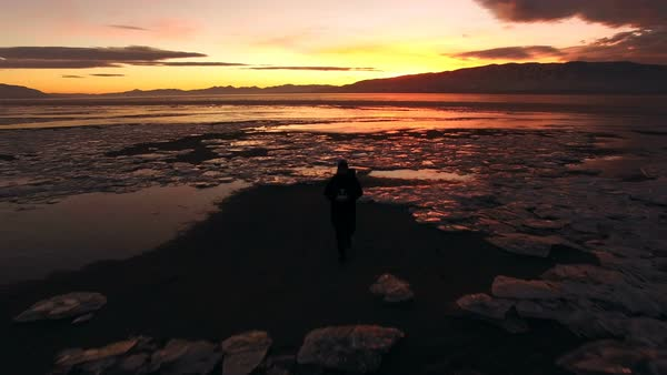 View of man walking over icy landscape at sunset while flying backwards. Royalty-free stock video