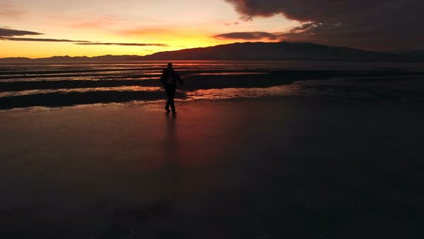 Silhouette of man walking across ice during sunset on Utah Lake. Royalty-free stock video