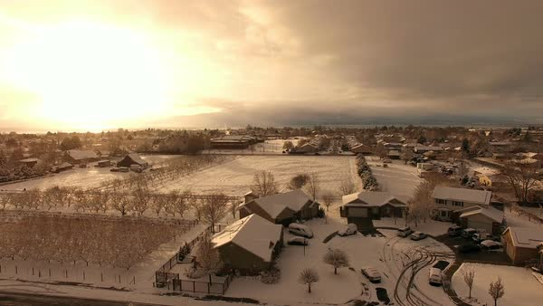 Aerial view over houses while snow is falling as the sun is setting on Christmas Day. Royalty-free stock video