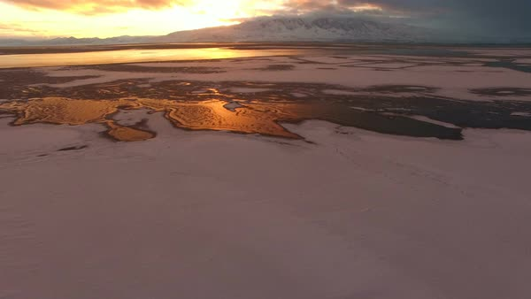 Flying over ice on lake panning upwards to view colorful sunset on Utah Lake. Royalty-free stock video