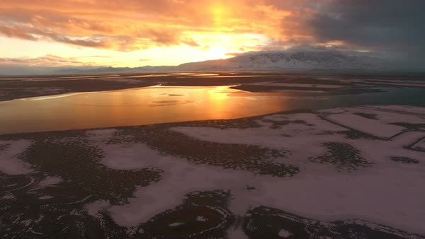 Aerial view of sunset over frozen lake panning down towards the ice in Utah. Royalty-free stock video