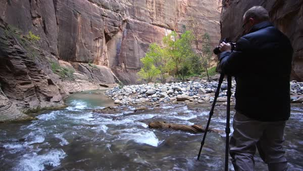 Photographer taking photos in the Zion Narrows and adjusting camera. Royalty-free stock video