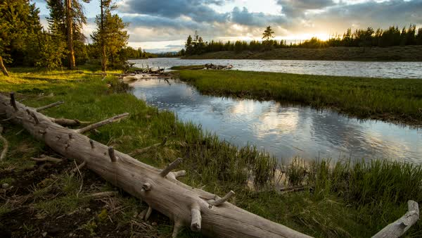 Timelapse as sun is setting along river in Yellowstone moving on slider. Royalty-free stock video
