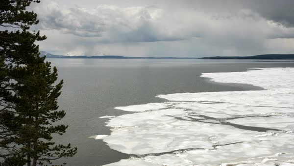 Clouds moving over icy lake in Spring as a timelapse over Yellowstone Lake Royalty-free stock video