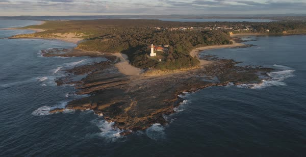 Magnificent aerial view of Norah Head lighthouse at low tide displaying reef along with sandy beach and an oxford blue ocean Royalty-free stock video
