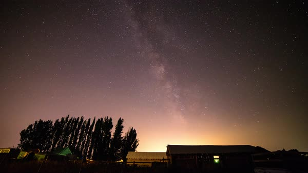 Spendid time lapse view of starry night sky in Idaho showing rural outbuildings and tree line silhouettes Royalty-free stock video