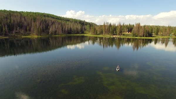 Aerial view of woman fishing from kayak over glassy lake Royalty-free stock video