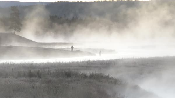 Wide view of 2 people through steam coming off winding river as they fly fish. Royalty-free stock video