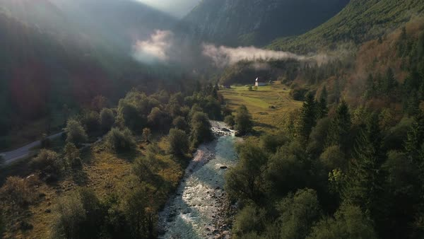 Flying backwards over the Soca River flowing through Lepena Valley as the sun shines through the thin fog and low clouds. Royalty-free stock video