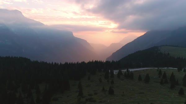 Sunrise aerial view looking towards foggy canyon in the Julian Alps as the sun lights up the clouds. Royalty-free stock video