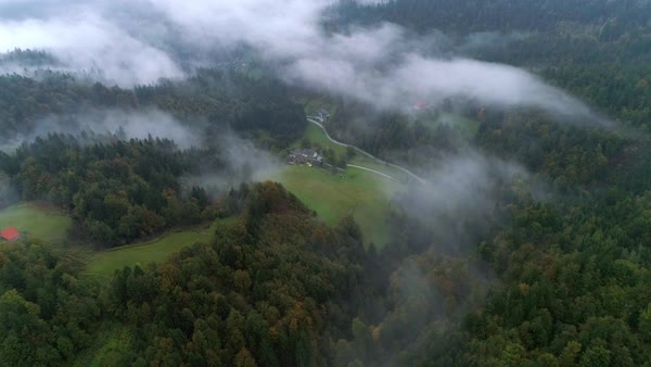 Aerial view flying over foggy forest panning down towards farm house on the edge of a forest in Skofja Loka, Slovenia. Royalty-free stock video