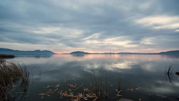 Timelapse overlooking Utah Lake as leaves move through the water, and colorful sunset sneaks sneaks in to light up the landscape. Royalty-free stock video