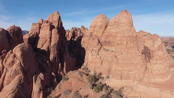 Aerial view flying through rock fins in Moab Utah then rising up and over to reveal the red rock desert landscape. Royalty-free stock video