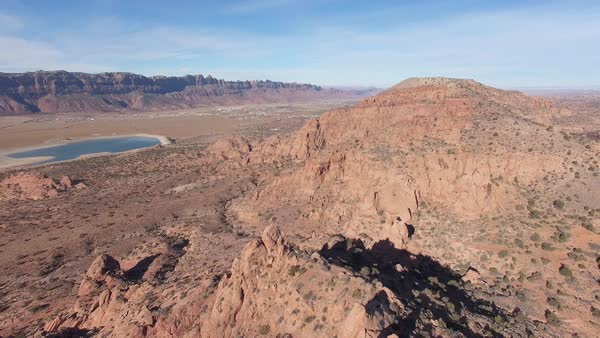 Aerial view of red rock desert landscape in Moab Utah flying backwards over tops of sandstone rock formations. Royalty-free stock video