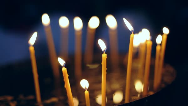 Votive candles burning in a darkened cathedral. Royalty-free stock video